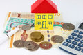 Danish property a toy house sitting on kroner notes with coins and a calculator a photograph illustrating house costs and finance Royalty Free Stock Photography