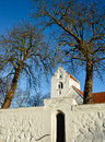 Danish village church two trees frames the tower of a classic with white plastered walls and red tiled roof Stock Photo