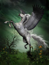 Dapple grey pegasus a takes to flight from a forest knoll with huge wing beats Stock Photo