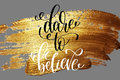 Dare to believe - hand lettering positive quote on golden brush