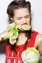 Daring funny girl with braids and red lips emotional eating cabbage beauty emotion face picture taken in the studio on a white Royalty Free Stock Photography