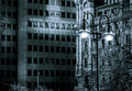 Dark ambiance business tower and historic building and night street lamp photo Stock Photos