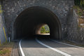 Dark automotive tunnel on turned rural asphalt road Royalty Free Stock Image