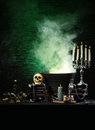Dark background with candles and a human skull green boiling water perfect to use as halloween card Royalty Free Stock Photos