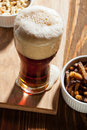Dark beer with snacks on wooden table Royalty Free Stock Image