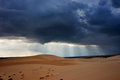 Dark black storm clouds with piercing sunrays covering desert landscape. Royalty Free Stock Photo