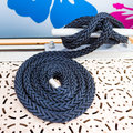 Dark blue coiled rope on a boat deck Stock Photos