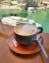 Dark blue cup of cappuccino on table overlooking the river, yachts and boats.  Morning breakfast. Royalty Free Stock Photo
