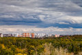 Dark blue rainy clouds over city in autumn storm and urban park Stock Photography