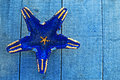 Dark blue starfish shape on blue decking background Royalty Free Stock Photos