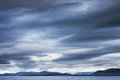 Dark blue stormy clouds over the mountains empty norwegian sea landscape Royalty Free Stock Images
