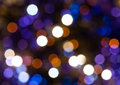 Dark blue and violet shimmering christmas lights abstract blurred background bokeh of electric garlands on xmas tree Stock Photography