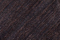 Dark brown background of a knitted textile material. Fabric with a striped texture closeup. Royalty Free Stock Photo