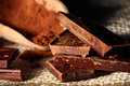 Dark chocolate pieces close up of in with cocoa on a wooden spoon Royalty Free Stock Photography