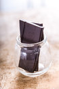 Dark cocoa solids chocolate in glas jar big chunks of a glass on rustic wood with back lighting Stock Photos