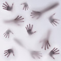 A dark and frightening silhouette of many different hands on a foggy moisture glass background Stock Photography