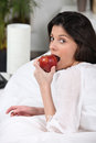 Dark-haired bourgeoise crunching apple Royalty Free Stock Photo