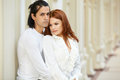 Dark-haired man and red-haired woman stand embraced Royalty Free Stock Photo