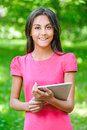 Dark haired young woman with e book portrait of beautiful smiling in pink dress against summer green park Stock Image