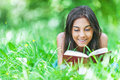 Dark haired young woman reading red beautiful smiling lying on grass and book against summer green park Royalty Free Stock Photos