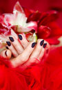 Dark manicure and red and white lilies Royalty Free Stock Photography
