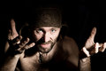 Dark portrait of scary evil sinister bearded man with smirk, makes various hand& x27;s signs and expresses different emotions Royalty Free Stock Photo