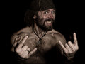 Dark portrait of scary evil sinister bearded man with smirk, shows sign of heavy metal. strange Russian man with a naked