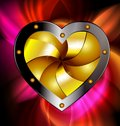 On a dark red background is a big golden metal heart Stock Photo