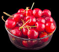 Dark red cherries in a brown transparent bowl isolated black background cutout Stock Photo