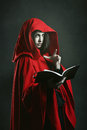 Dark red hooded witch reading a book Royalty Free Stock Photo