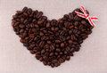 Dark roasted coffee beans  in the shape of a heart with a red bo Stock Images