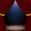Dark room with red curtains and stage lighting a lighted wooden Stock Image