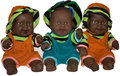 Dark skinned baby dolls three colorfully dressed smiling Royalty Free Stock Photography