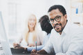 Dark skinned entrepreneur wearing glasses, working in modern office.African american man in white shirt looking and smiling at the Royalty Free Stock Photo