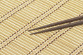 Dark wooden chopsticks on bamboo mat closeup Royalty Free Stock Photography