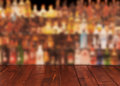 Dark wooden table against interior of bar with alcohol bottles Royalty Free Stock Photo
