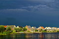 Lakeside holiday resort by dark-blue sky at sunset and imminent storm Royalty Free Stock Photo