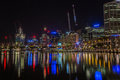 Darling harbour at night colourful light reflections in the water in sydney is a lively place with many bars and Stock Photos