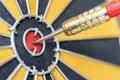 Dart arrow hitting in target bullseye of dartboard Royalty Free Stock Photo