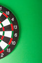Dart board with black and white sections on green background Stock Photo