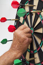 Dart board with darts man pulling off off Stock Photography