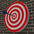 Dart hitting center target on dartboard brick background Royalty Free Stock Images