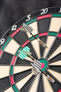 Dartboard and arrows colorful darts hit on dark background Royalty Free Stock Photos