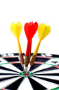 Dartboard with darts in yellow and red colors are on the target of a Stock Photo