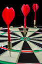 Dartboard red darts with in dark Stock Photo