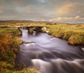 Dartmoor long exposure shot of an ancient clapper bridge across a remote river on devon Stock Photo