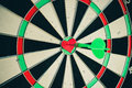 Darts arrow in the target center of the heart toned image Royalty Free Stock Image