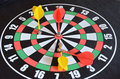 Darts target with colored arrows on the black background Stock Images