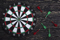 The darts on wooden background dark Royalty Free Stock Photos