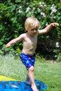 Das Kleinkind springend über Water-slide Lizenzfreie Stockfotografie